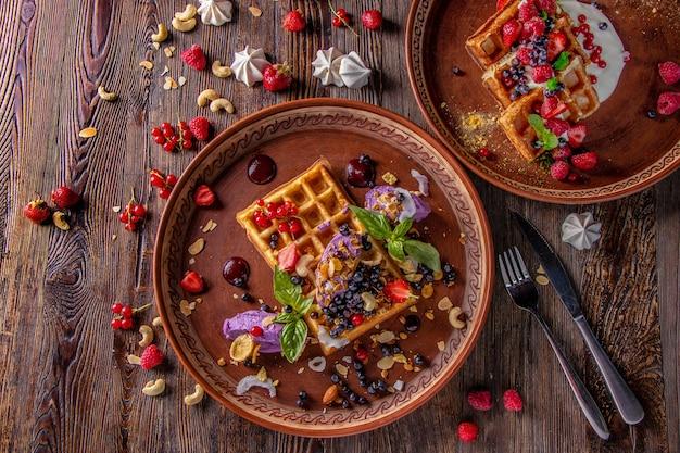 Odmiany belgijskich gofrów z kremem jagodowo-serowym, muesli, orzechami i świeżymi jagodami