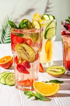 Odmiany lemoniady z różnymi owocami i syropami na drewnianym stole w porannym słońcu