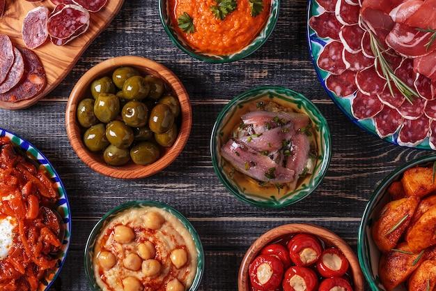 Odmiany plasterki jamon, chorizo, salami, miski z oliwkami, papryką, anchois, pikantne ziemniaki, puree z ciecierzycy na drewnianym stole.
