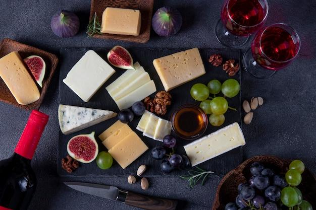 Odmiany serów, winogrona, figi i orzechy na łupkowym talerzu. wina przekąski na świąteczne przyjęcie. widok z góry