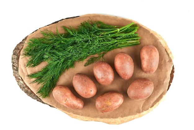 Odmiany zieleni z ziemniakami na drewnianym talerzu.