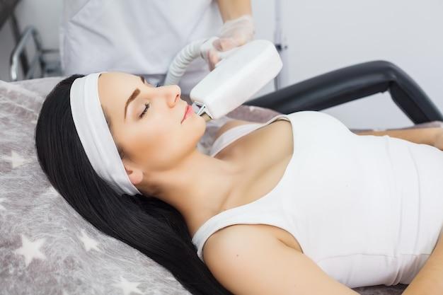 Odmładzający zabieg na twarz. model coraz masażu terapeutycznego liftingującego w salonie piękności. złuszczanie, odmładzanie i nawilżanie. model i lekarz. kosmetyka.