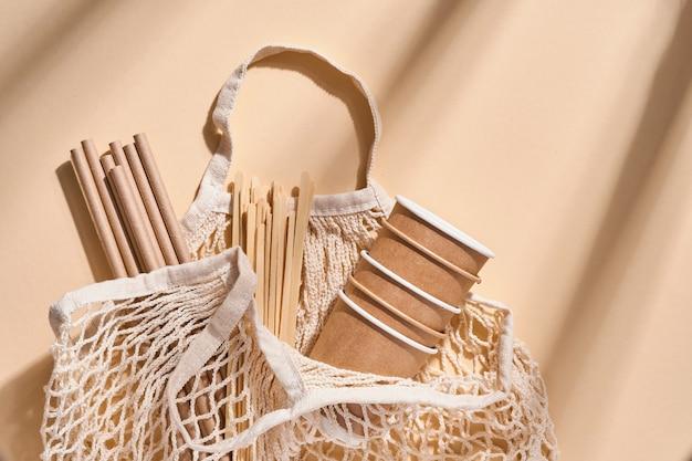 Odnawialne pojedyncze przedmioty do użytku domowego, bambusowe lub papierowe słomki, jednorazowe kubki i drewniane mieszadełka do kawy w kolorze beżowym. zero marnowania. widok z góry.