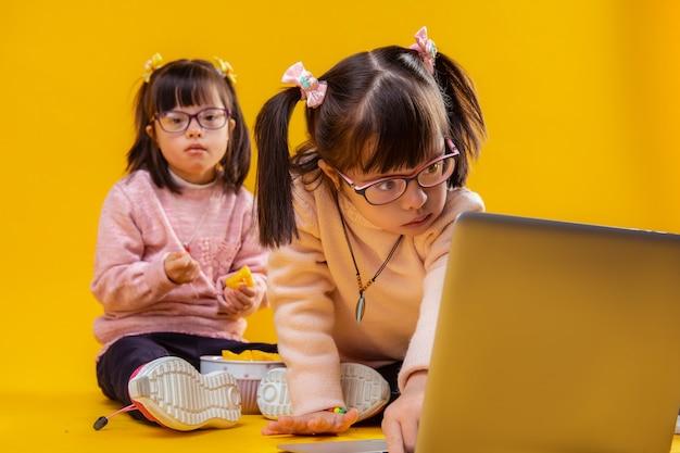 Odnośnie kreskówek. dwie ładne siostry cierpiące na zaburzenia psychiczne bawi się na podłodze z laptopem i jedzeniem