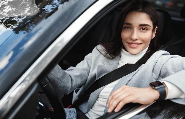 Odnosząca sukcesy bizneswoman prowadzi samochód do pracy, zapina pasy i formalną odzież