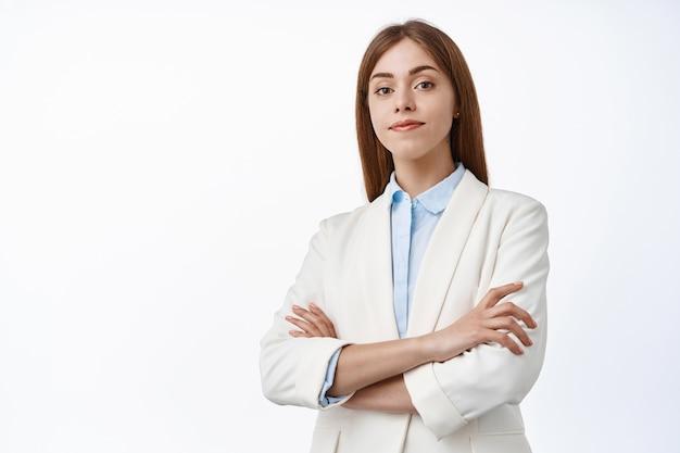 Odnosząca sukcesy bizneswoman w białym garniturze, skrzyżowane ramiona na piersi, uśmiech z pewnością siebie, spójrz na przód zdecydowany, biała ściana