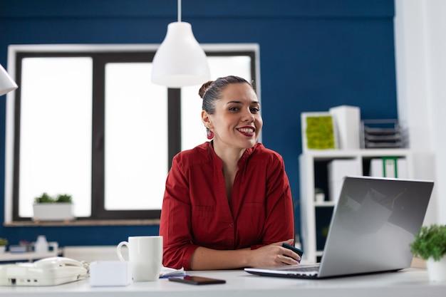Odnosząca sukcesy bizneswoman w biurze firmy finansowej, patrząc na kamerę siedzącą przy biurku