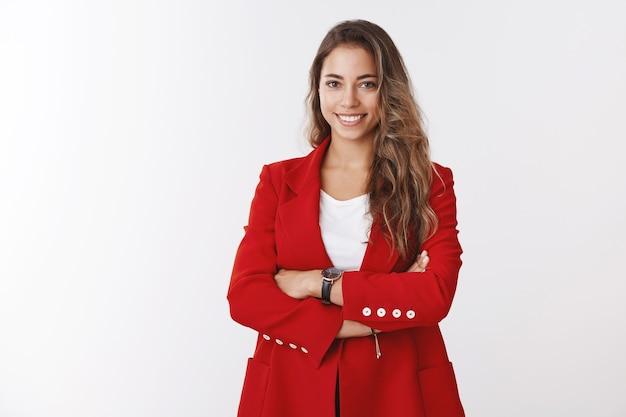 Odnosząca sukcesy, dobrze wyglądająca bizneswoman, nosząca czerwoną kurtkę z krzyżem, pewna siebie, uśmiechnięta pewna siebie, asertywna, wiedząca, jak pracują klienci, zarządzająca własnym biznesem, biała ściana