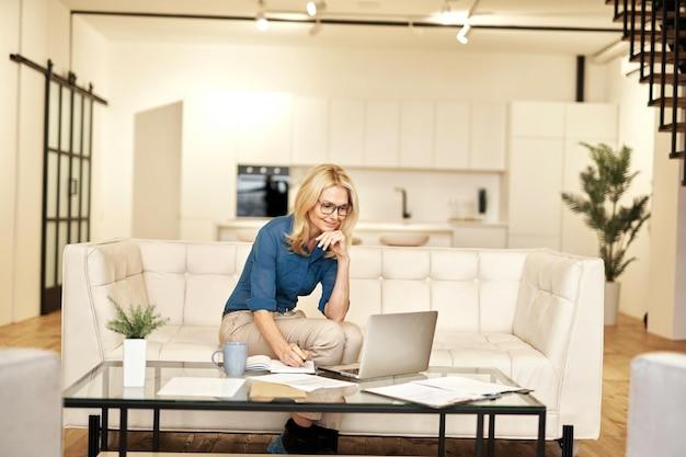 Odnosząca sukcesy dojrzała kobieta biznesu w stroju casual, uśmiechając się, robiąc notatki, pracując w domu, podczas gdy