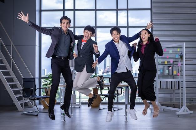 Odnosząca sukcesy firma z szczęśliwymi pracownikami jumping for joy grupa azjatyckich ludzi biznesu o różnych płciach (lgbt) świętuje wolność i wsparcie lgbt w sali konferencyjnej w biurze