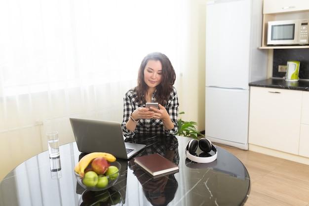 Odnosząca sukcesy kobieta-przedsiębiorczyni z nową firmą online, pracująca w domu w kuchni na swoim laptopie