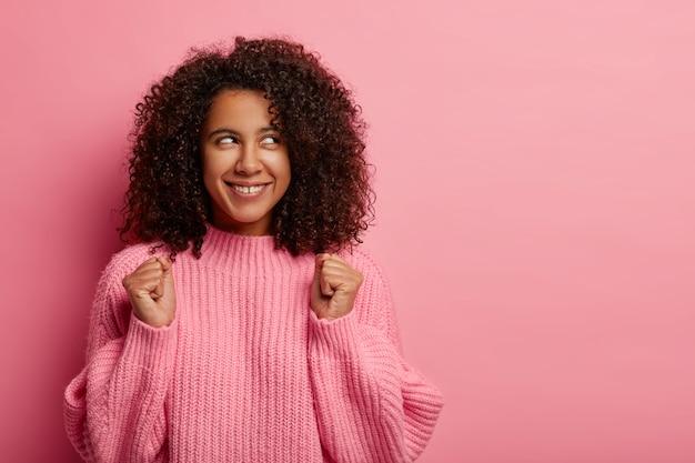 Odnosząca sukcesy młoda afroamerykańska nastolatka świętuje osiągnięcie, podnosi zaciśnięte pięści, ubrana w duży zimowy sweter, uśmiecha się szeroko, patrzy na bok, odizolowana na różowym tle.
