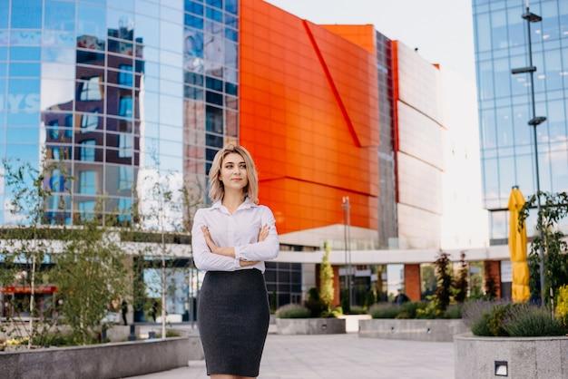 Odnosząca sukcesy młoda kobieta biznesu obok nowoczesnych wielokondygnacyjnych budynków biznesowych.