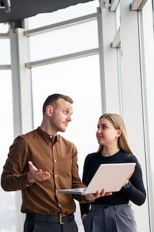 Odnosząca sukcesy pracownica biurowa z koleżanką z netbookiem stoi w wieżowcu na tle okna z widokiem na miasto. architekci miasta patrzący na laptopa zadowoleni z projektu