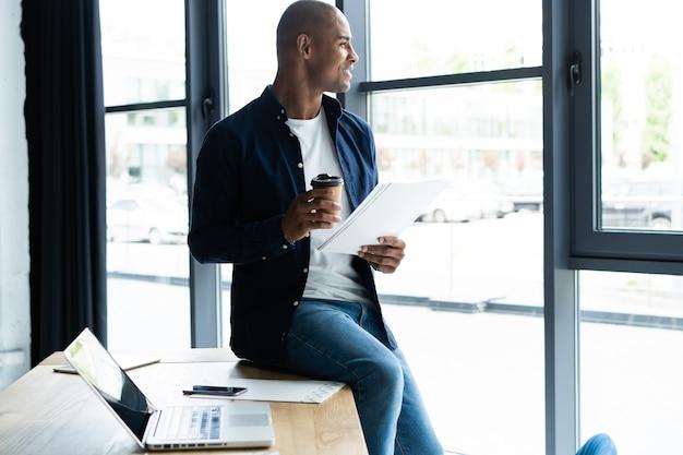 Odnoszący sukcesy afrykański przedsiębiorca studiujący dokumenty z uważnym i skoncentrowanym spojrzeniem, pijący kawę w kawiarni. ciemnoskóry biznesmen skoncentrowany na kwestiach związanych z pracą, podpisującym dokumenty do umów biznesowych