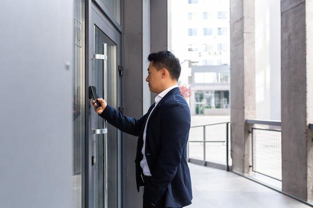 Odnoszący sukcesy azjatycki biznesmen otwiera drzwi centrum biurowego za pomocą smartfona i aplikacji nfc