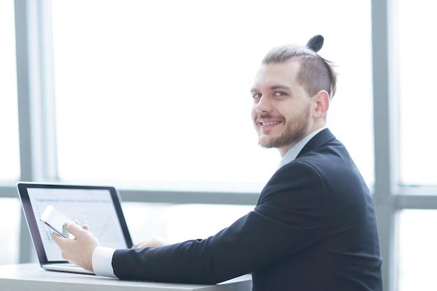 Odnoszący sukcesy biznesmen pije kawę, siedzi przy swoim biurku .przerwa na kawę
