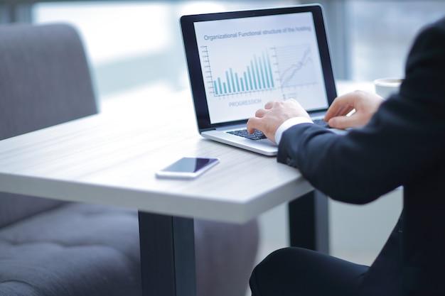 Odnoszący sukcesy biznesmen pracujący na laptopie z dokumentami finansowymi