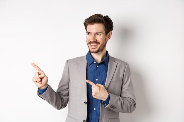 Odnoszący sukcesy biznesmen w szarym garniturze, wskazując palcami w lewo i patrząc na baner, uśmiechając się pewnie, pokazując reklamę, stojąc na białym tle.