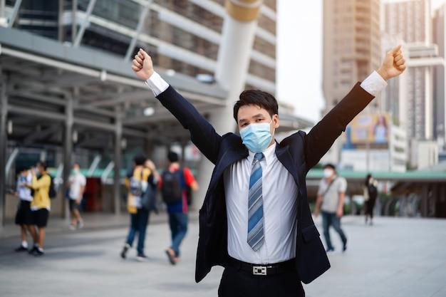 Odnoszący sukcesy biznesmen z podniesionymi rękami i maską medyczną podczas pandemii koronawirusa w mieście