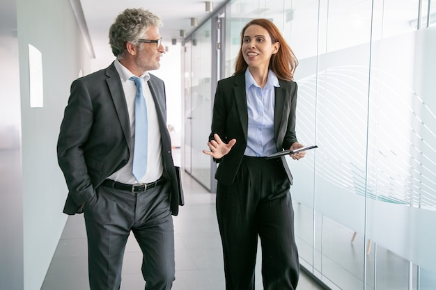 Odnoszący sukcesy biznesmeni przechadzający się po biurowym korytarzu i rozmawiający