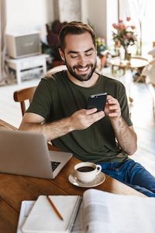 Odnoszący sukcesy dojrzały mężczyzna w codziennej odzieży za pomocą laptopa i smartfona podczas pracy w mieszkaniu