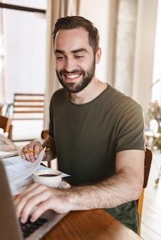 Odnoszący sukcesy dojrzały mężczyzna w swobodnym ubraniu zapisujący notatki na papierze i korzystający z laptopa podczas pracy w mieszkaniu