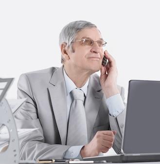 Odnoszący sukcesy, doświadczony biznesmen z telefonem komórkowym siedzącym przy biurku .isolated on white