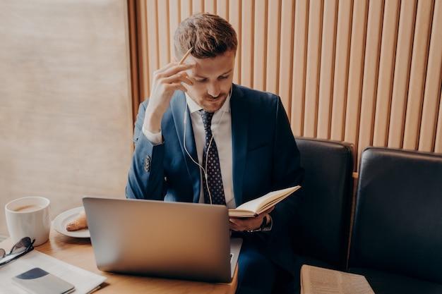 Odnoszący sukcesy finansista w eleganckim garniturze z przemyślanym spojrzeniem w słuchawkach i laptopie pracujący online nad prezentacją biznesową, siedząc w kawiarni nad filiżanką latte i sprawdzając notatki w skoroszycie