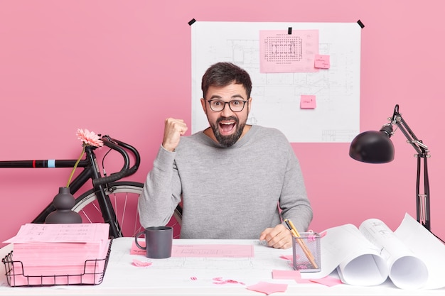 Odnoszący sukcesy inżynier zaciska pięści głośno wykrzykuje raduje się z ukończenia swojego projektu architektonicznego pozuje przy pracach biurowych z planami robi notatki na naklejkach. koncepcja sukcesu pracy ludzi