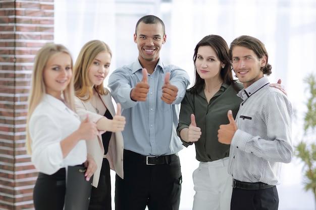 Odnoszący sukcesy międzynarodowy zespół biznesowy pokazujący kciuk w górę