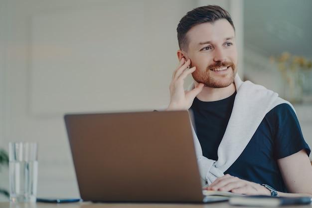 Odnoszący sukcesy młody biznesmen noszący słuchawki patrząc na bok, czując się szczęśliwy i uśmiechnięty po spotkaniu online. freelancer myślący o pozytywnym wyniku rozmowy podczas pracy na laptopie w domu