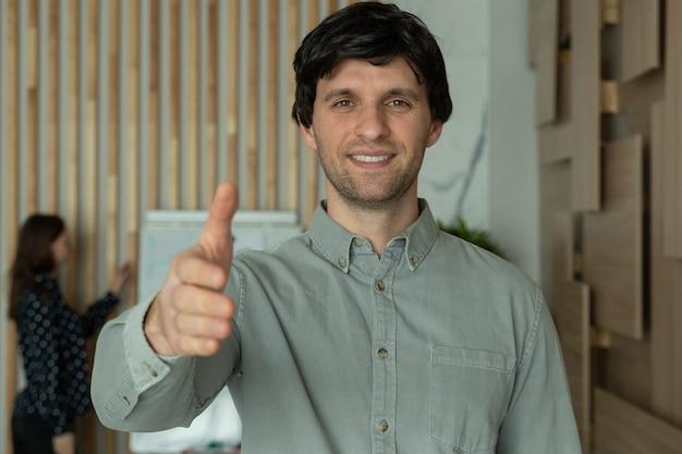 Odnoszący sukcesy młody biznesmen wyciągając rękę do uścisku dłoni w biurze patrzy w kamerę