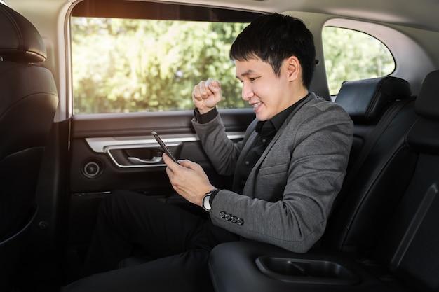 Odnoszący sukcesy młody biznesmen za pomocą smartfona siedząc na tylnym siedzeniu samochodu