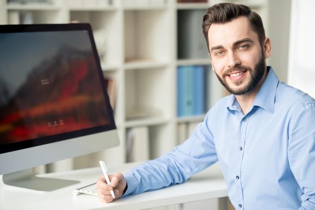 Odnoszący sukcesy młody brodaty projektant lub analityk patrzy na ciebie podczas planowania pracy przy biurku w biurze