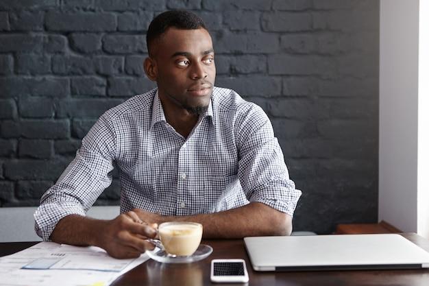 Odnoszący sukcesy, młody, ciemnoskóry ceo pije poranną kawę, siedząc przy stoliku z laptopem przy kawiarnianym stoliku