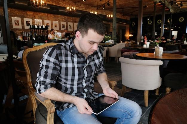 Odnoszący sukcesy młody człowiek w ciemnej kraciastej koszuli w kawiarni prowadzi interesy. młody hipster, trzymając w ramionach i patrząc na cyfrowy tablet, uśmiechając się. pracownik biurowy na lunch.