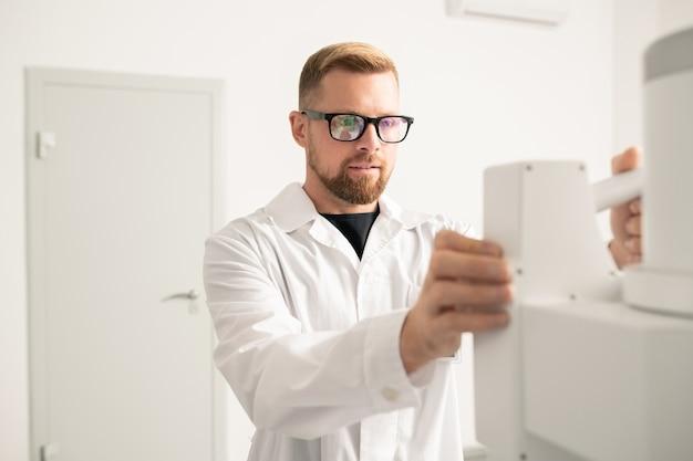 Odnoszący sukcesy młody lekarz w białym fartuchu i okularach stoi przed współczesnym sprzętem medycznym podczas pracy w klinikach