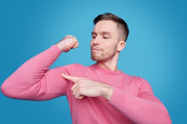 Odnoszący sukcesy młody sportowy mężczyzna w codziennym stroju, wskazując na swój mięsień na ramieniu z dumnym wyrazem