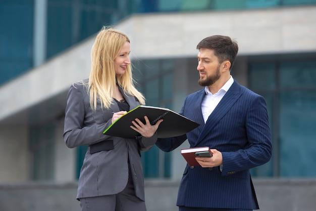 Odnoszący sukcesy partnerzy biznesowi mężczyzna i kobieta obok budynku biznesowego z dokumentami w rękach omawiających projekty biznesowe