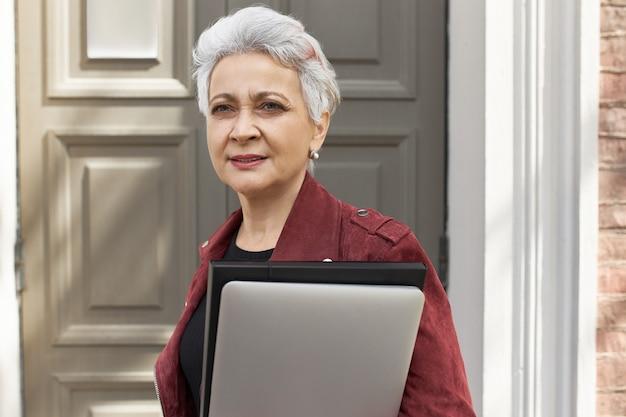 Odnoszący sukcesy, pewny siebie zarządca nieruchomości w średnim wieku ze stylową krótką fryzurą i laptopem