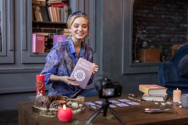 Odnoszący sukcesy pisarz. szczęśliwa miła kobieta uśmiecha się, pokazując swoją książkę widzom