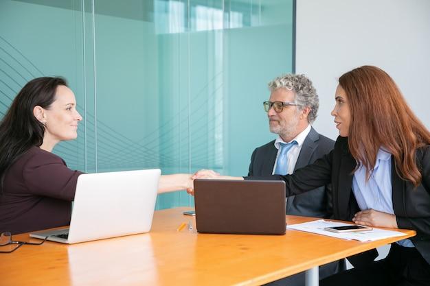 Odnoszący sukcesy pracodawcy w średnim wieku siedzą i ściskają ręce