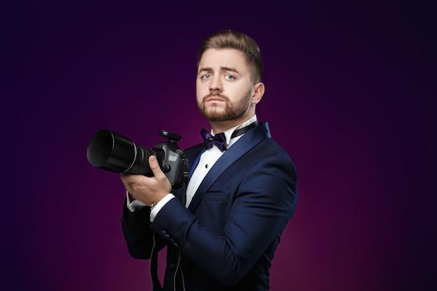 Odnoszący sukcesy profesjonalny fotograf w smokingu używa cyfrowego aparatu dslr na ciemnym tle