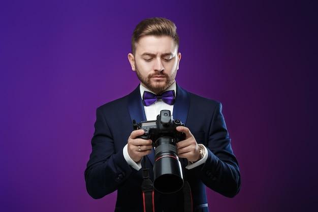 Odnoszący sukcesy profesjonalny fotograf w smokingu używa cyfrowego aparatu dslr w ciemności