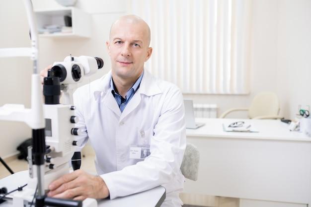 Odnoszący sukcesy profesjonalny optyk w białym fartuchu patrzy na ciebie podczas pracy z nowym sprzętem do badania wzroku
