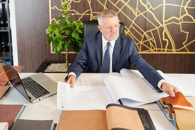 Odnoszący sukcesy starszy kierownik fabryki mebli wybierający tkaninę obiciową do nowej kolekcji sof i foteli