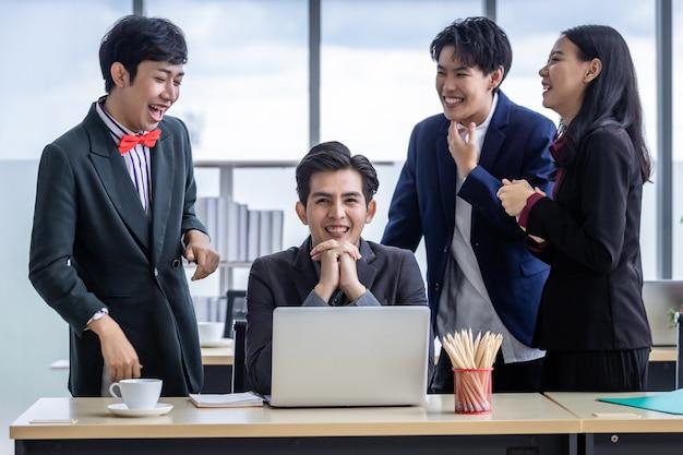 Odnoszący sukcesy szczęśliwi pracownicy grupa azjatyckich biznesmenów o różnej płci (lgbt) klaszcz w dłonie i gratuluj biznesmenowi, gdy na laptopie w sali konferencyjnej widzi udany biznesplan