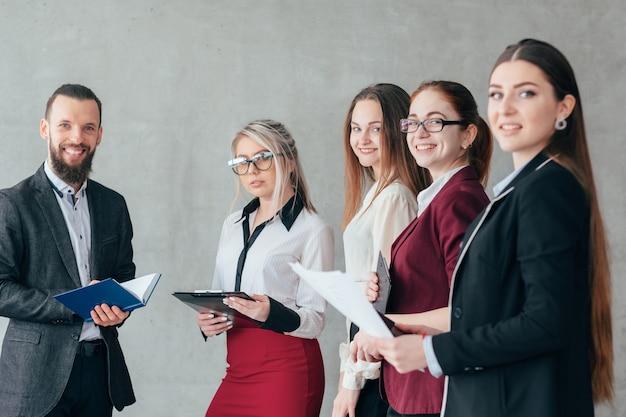Odnoszący sukcesy trener biznesu. zaawansowane szkolenie korporacyjne. uśmiechnięci członkowie zespołu kobiet w obszarze roboczym.