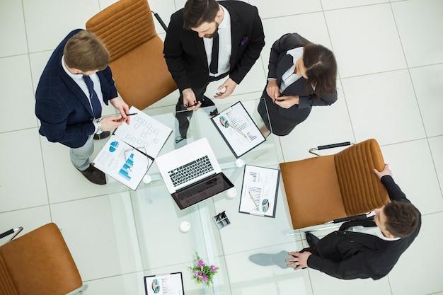 Odnoszący sukcesy zespół biznesowy omawiający grafikę marketingową na spotkaniu roboczym